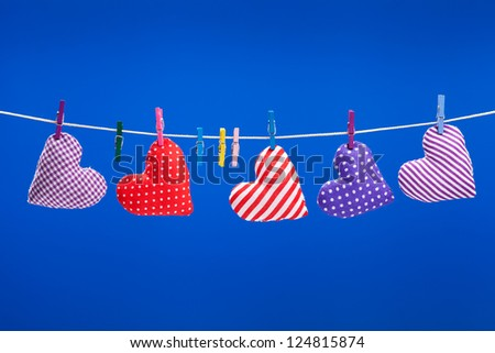 hearts hanging on a clothesline with clothespins, blue background - stock photo
