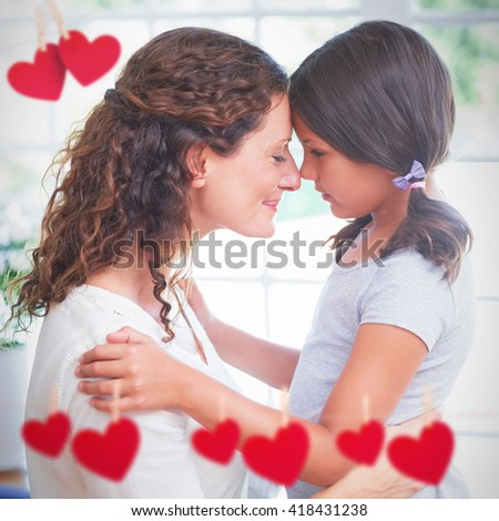 Hearts hanging on a line against happy mother and daughter embracing - stock photo