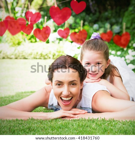 Hearts hanging on a line against mother and daughter smiling at camera - stock photo