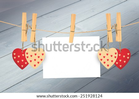 Hearts hanging on the line against bleached wooden planks background