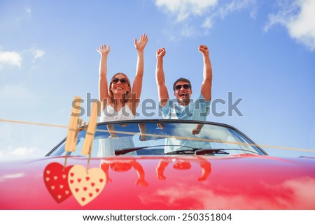 Hearts hanging on the line against crazy couple standing in red cabriolet - stock photo