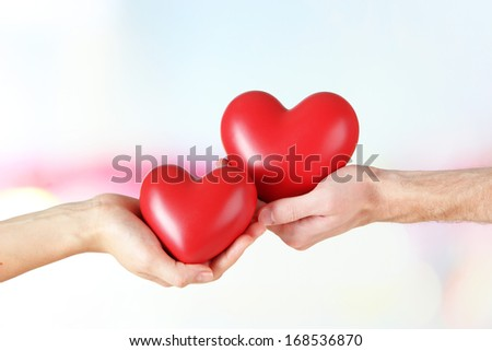 Hearts in hands on light background - stock photo