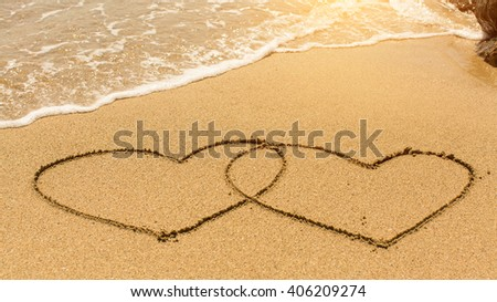 Hearts in the sand drawn by hand in the surf.