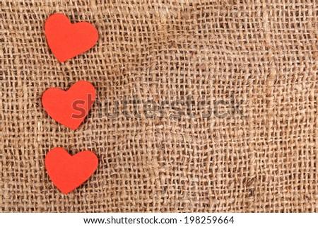 Hearts made of felt on sacking background - stock photo