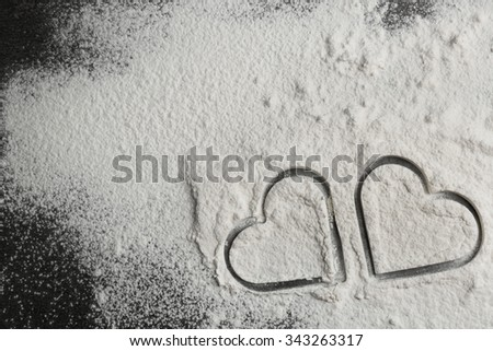 Hearts of flour on gray background