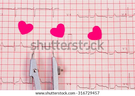 Hearts of paper and calipers lying on electrocardiogram graph, ecg heart rhythm, medicine and healthcare concept