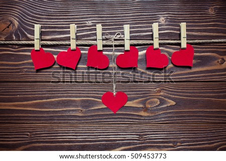 hearts on the clothespin on the wooden background
