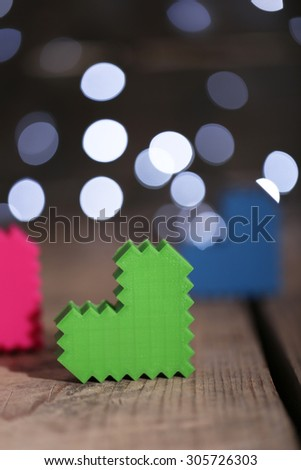 Hearts on wooden table and blurred background with lights