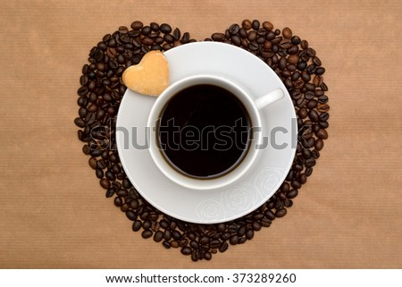 Hearts shaped coffee beans, cup of coffee and cookies on a paper parchment background - stock photo