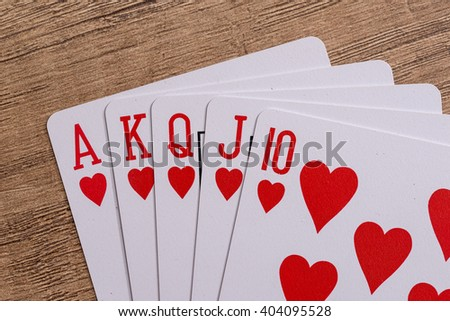 Hearts suit playing cards on wooden desk - stock photo