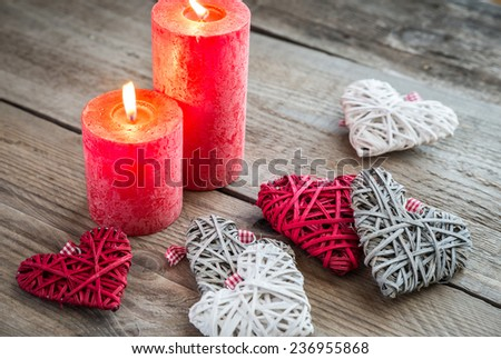Hearts with burning candles on the wooden background - stock photo