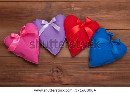 Hearts with ribbons of different colors on a wooden background. - stock photo