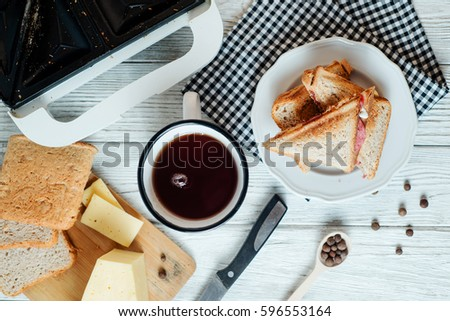 Hearty and traditional breakfast, sandwiches with rye toast, sausage, cheese, spices and black tea on a light wooden background