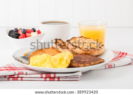 Hearty breakfast of scrambled eggs, sausage, fruit and coffee. - stock photo