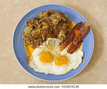 hearty breakfast plate with hash browns two eggs and bacon - stock photo