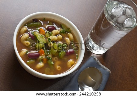 Hearty winter minestrone soup and glass of refreshing water - stock photo