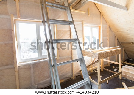 Heat insulation and wooden logs lathing ready for Finishing made of tongue and groove planks. An interior view of unfinished home inside. Work in process - stock photo