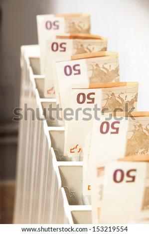 heat radiator spending gas money - stock photo