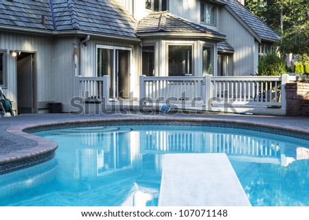 Heated outdoor swimming pool with large home in background with green trees - stock photo
