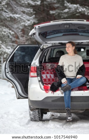 Heated up young Caucasian woman in unbutton fur coat sits in trunk of own car. Resting and breathing in winter wood