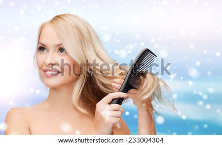 heath, people, haircare and beauty concept - beautiful young woman with bare shoulders combing her hair over blue sky, snow and clouds background - stock photo