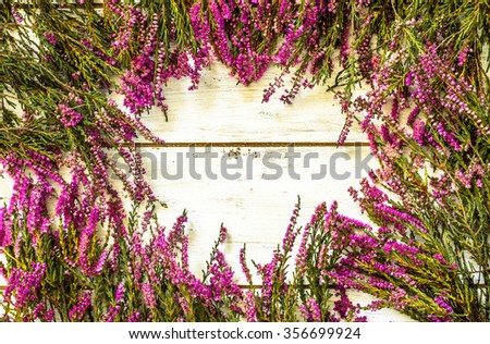 Heather flowers frame on shabby wood background useful as greeting card. - stock photo