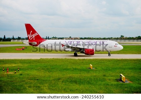 HEATHROW, ENGLAND --MAY 2014-- An Airbus A320 from the British airline Virgin Atlantic is getting ready for takeoff on the tarmac of London Heathrow International Airport (LHR). - stock photo