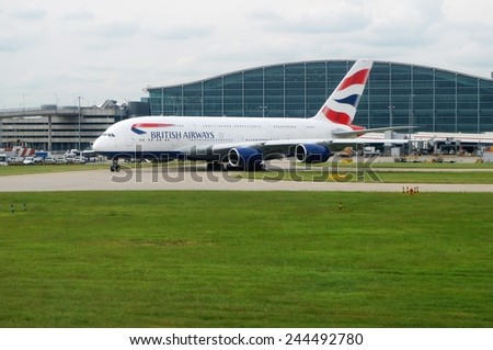 HEATHROW, ENGLAND --21 MAY 2014-- An Airbus A380 jumbo jet airplane gets ready for takeoff at London Heathrow Airport (LHR) Terminal 5. - stock photo