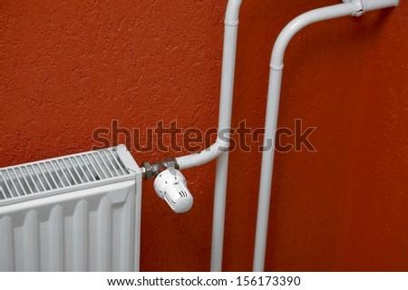 Heating radiator detail against orange wall - stock photo