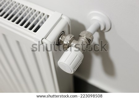 Heating radiator detail against orange wall - stock photo