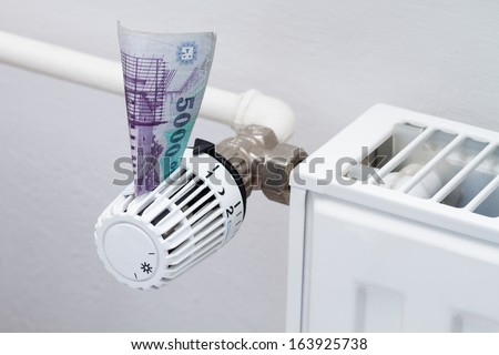 heating thermostat with money, hungarian forint, expensive heating costs concept - stock photo