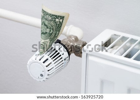 heating thermostat with money, one dollar, expensive heating costs concept - stock photo