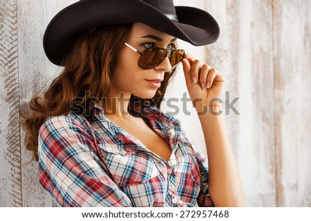 Heating up the wild west. Beautiful young cowgirl adjusting her eyewear and looking at camera while standing against the wooden background - stock photo
