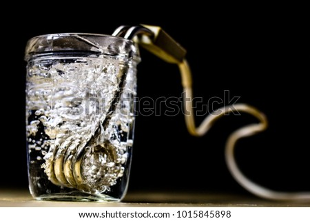 Heating water in a glass after mustard. The old method of brewing tea. Black background.