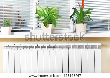 Heating white radiator radiator with flower and window
