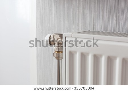 Heating white radiator with adjuster of warming in living room. - stock photo