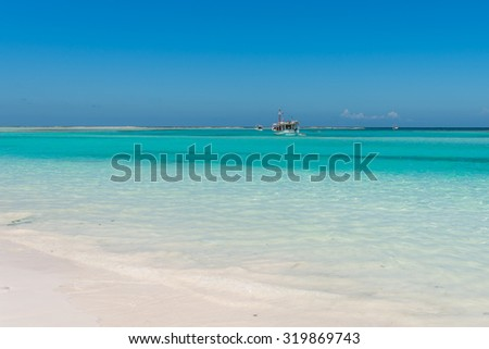 Heavenly-looking solitary beach with turquoise colored water and fishing boat in the Caribbean Sea. La Tortuga (Turtle) island, Venezuela.