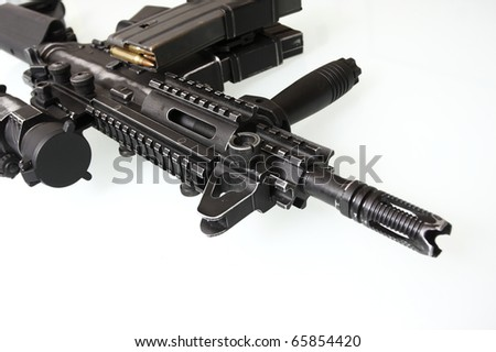 Heavily used military M16 rifle with short barrel on a white background. - stock photo