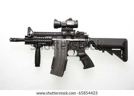 Heavily used military M16 rifle with short barrel on a white background.