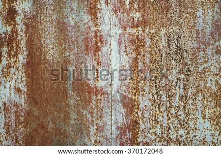 Heavily worn peeled rusty wall. - stock photo