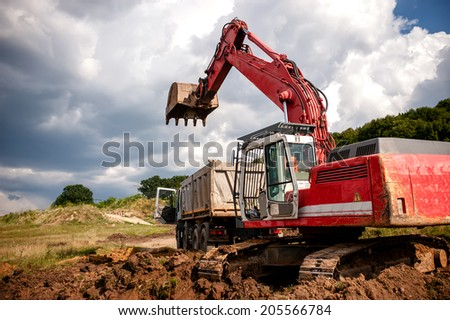Heavy bulldozer and excavator loading and moving red sand or soil on road construction site or quarry - stock photo