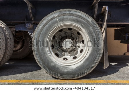 Heavy cargo truck wheel close up covered in dirt weathered and worn rubber tyre front face view horizontal
