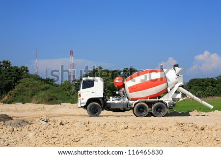 Heavy concrete truck on construction site against blue sky - stock photo