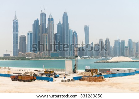 Heavy construction equipment stands by at a waterfront development site near a major metropolitan city, with tall, urban, highrise buildings in the background.  - stock photo