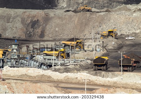 heavy construction tipper trucks dump coal to the conveyor at the lignite opencast mining - stock photo