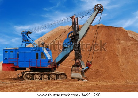 Heavy digger electric excavator standing in sandpit with huge bucket on the ground - stock photo
