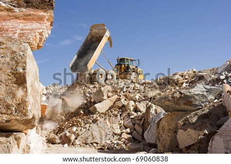 Heavy dump truck against blue sky operating in a marble quarry