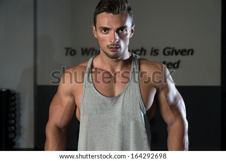 Heavy Duty. Body Builder Workout On Cable Machine. Standing Low Pulley Deltoids Raise - stock photo