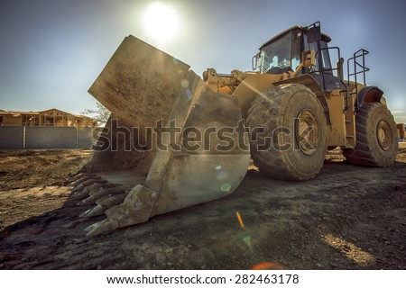 Heavy duty construction digger excavator equipment with sun flare. - stock photo