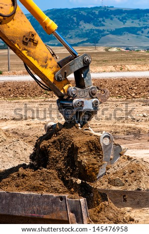 heavy duty construction excavator loading sand into a dumper truck - stock photo